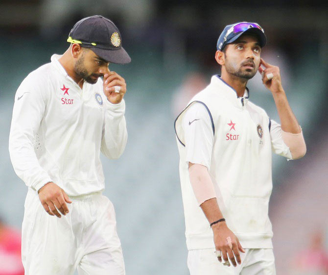 Virat Kohli and Ajinkya Rahane of India leave the field at the conclusion of day two of the First Test against Australia at Adelaide Oval