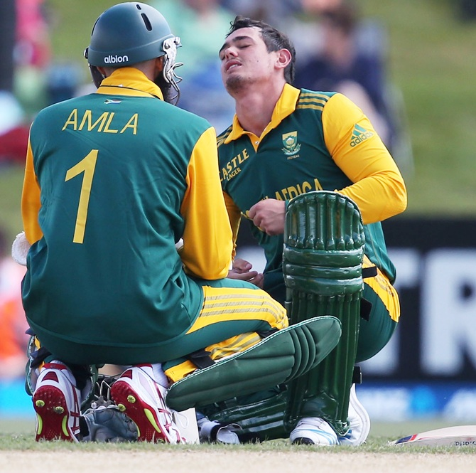 Quinton de Kock of South Africa is attended to by teammate Hashim Amla