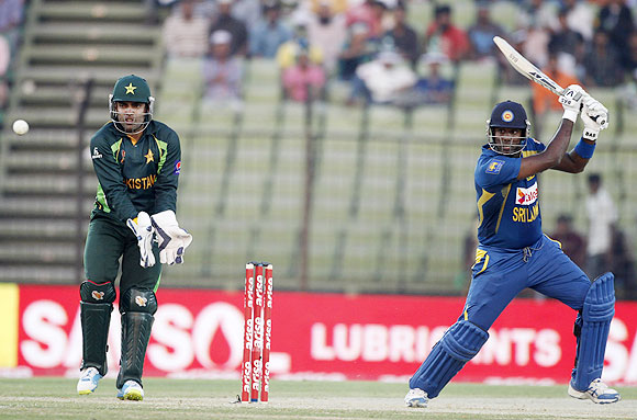 Sri Lanka's captain Angelo Mathews plays a shot as Pakistan's wicketkeeper Umar Akmal (L) watches during their One-day International at the 2014 Asia Cup in Fatullah on Tuesday