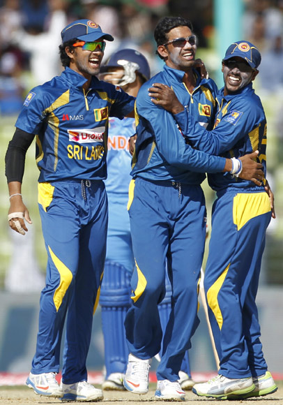 Sri Lanka's fielders congratulate Sachithra Senanayeke (second right) after he dismissed India's Rohit Sharma