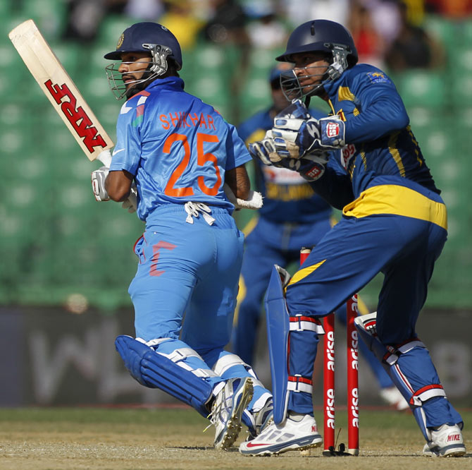 India's Shikhar Dhawan (left) plays a ball as Sri Lanka's wicketkeeper Kumar Sangakkara watches