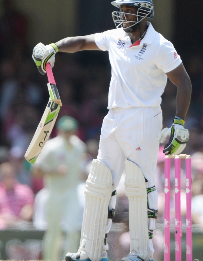 Michael Carberry of England holds up his broken bat