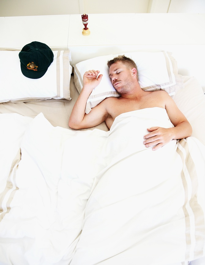 David Warner sleeps next to his baggy green cap and a replica Ashes urn