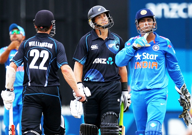 Ross Taylor of New Zealand reacts as MS Dhoni of India walks past