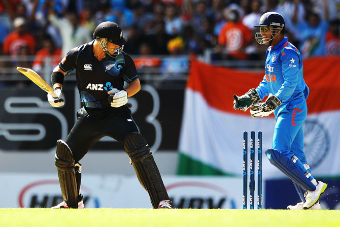 Corey Anderson of New Zealand looks at the stumps after being bowled by Ravichandran Ashwin of India as MS Dhoni celebrates