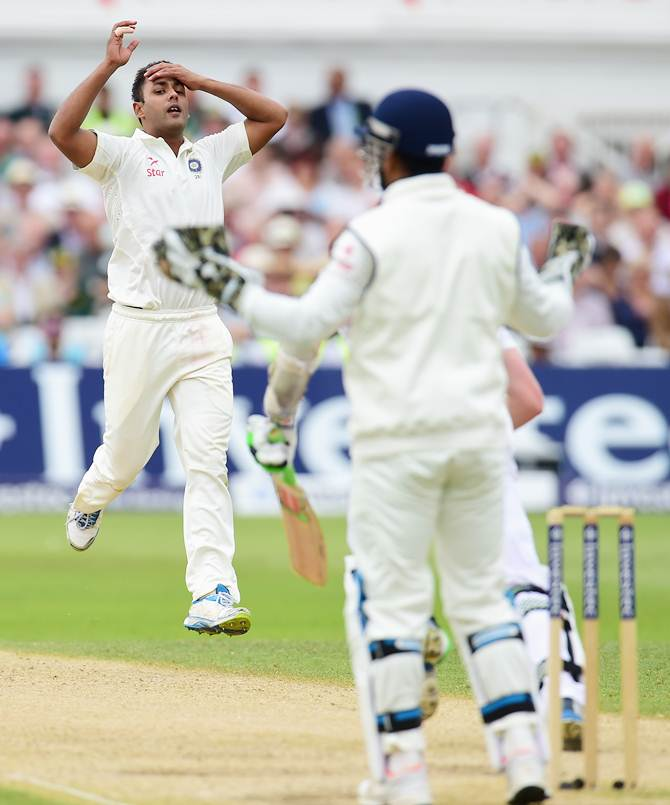 India bowler Stuart Binny and wicketkeeper Mahendra Singh Dhoni react after Sam Robson edges a delivery