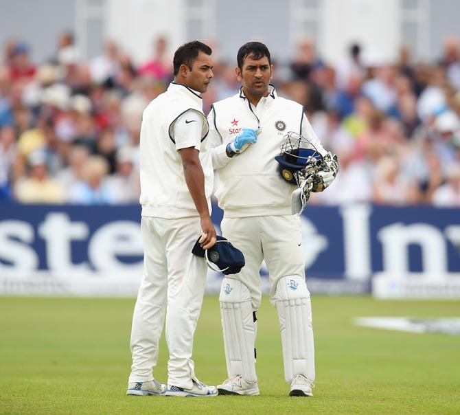 Mahendra Singh Dhoni (right) speaks to Stuart Binny