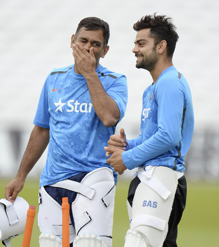 India's captain Mahendra Singh Dhoni (left) and Virat Kohli talk during a training session