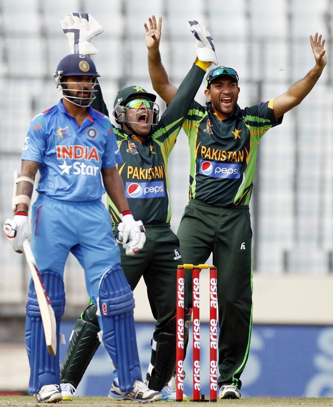 Shikhar Dhawan (left) looks on as wicketkeeper Umar Akmal and Shoaib Maqsood (right) appeal