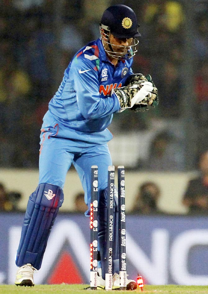 India's captain and wicketkeeper Mahendra Singh Dhoni breaks the wicket to dismiss Pakistan's Ahmed Shehzad