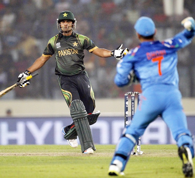 Pakistan's captain Mohammad Hafeez, left,  tries to take a run as India's captain and wicketkeeper MS Dhoni throws a ball