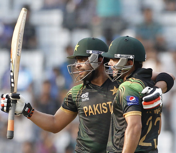 Pakistan's Umar Akmal celebrates after scoring a half century against Australia as teammate and brother Kamran Akmal (right) congratulates him
