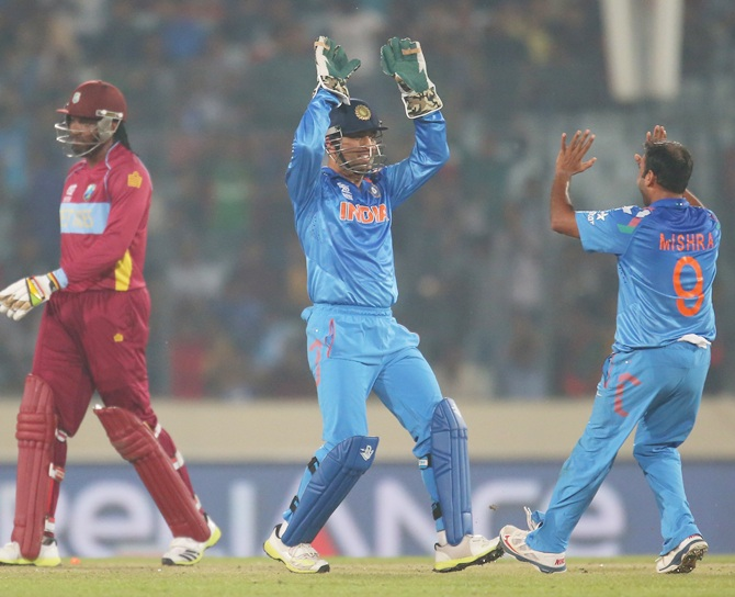Mahendra Singh Dhoni, centre, celebrates after running out Chris Gayle of the West Indies