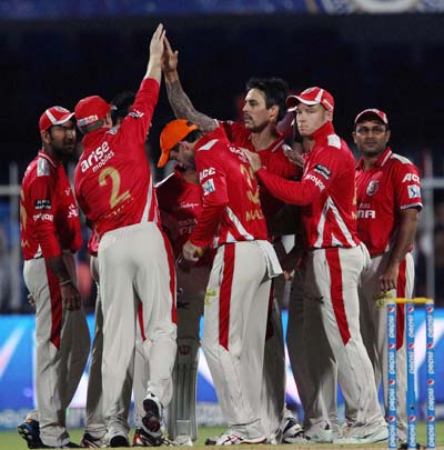 Kings XI Punjab players celebrate a dismissal by Mitchell Johnson