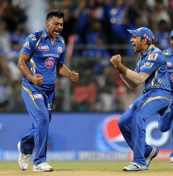 Praveen Kumar (left) and Rohit Sharma celebrate the wicket of Brendon McCullum.
