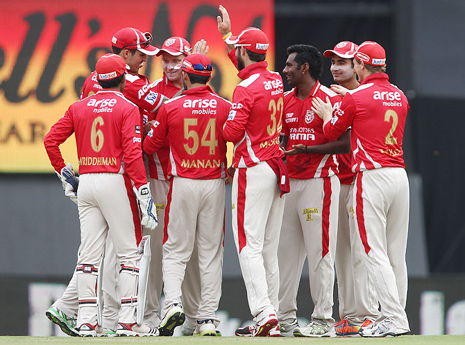 Akshar Patel and Parvinder Awana of the Kings XI Punjab are congratulated after dismissing Dinesh Karthik