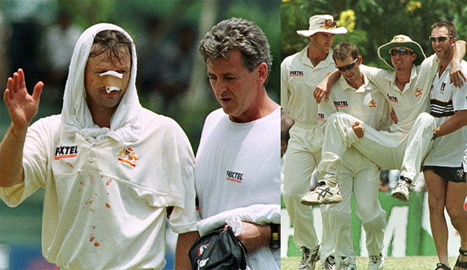 Australian captain Steve Waugh (left), with physiologist Errol Alcot, waves to the crowd before leaving the field after colliding with teammate Jason Gillespie in an attempt to take a catch to dismiss Sri Lankan batsman Mahela Jayawardena on the second day of the first Test at the Asgiriya stadium in central Kandy on September 10 1999. Australian fielder Jason Gillespie is carried off the field after colliding with Steve Waugh
