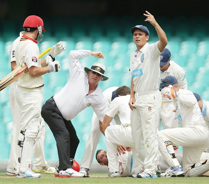Phillip Hughes of South Australia is helped by New South Wales players after falling to the   ground after being struck in the head by a delivery