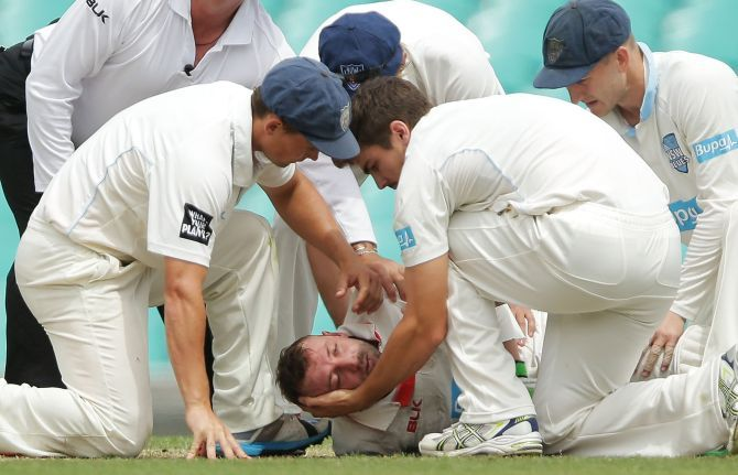 Phillip Hughes of South Australia is helped by New South Wales players