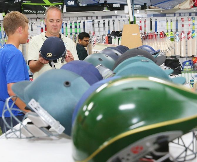 A father and son look at cricket helmets