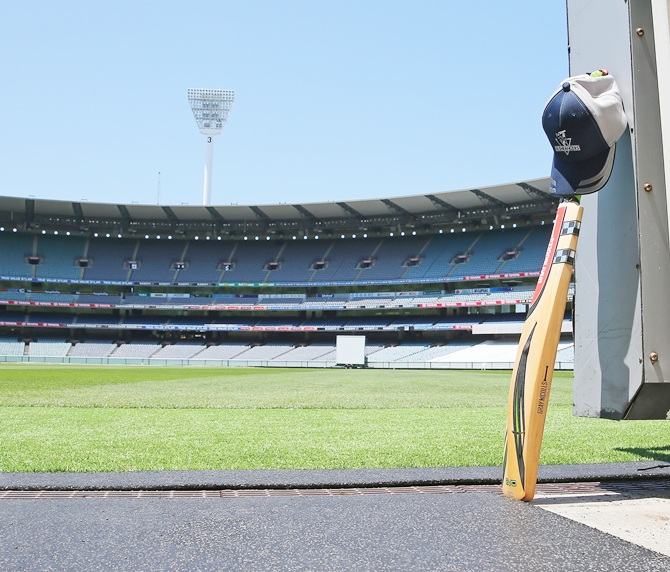 A cricket bat and cap left by a Cricket Victoria player sits in the players tunnel at the   Melbourne Cricket Ground as people remember Phillip Hughes by placing their bat and cricket   cap out the front of their homes as a sign of respect