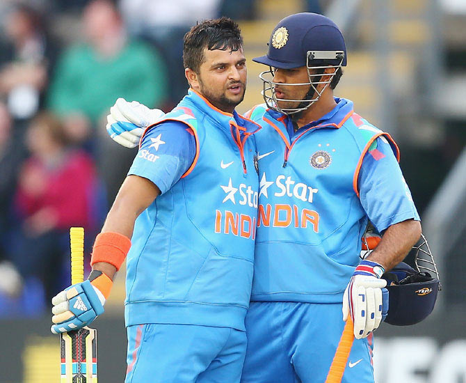 Suresh Raina (left) of India is congratulated by captain Mahendra Singh Dhoni after reaching his century in Cardiff.