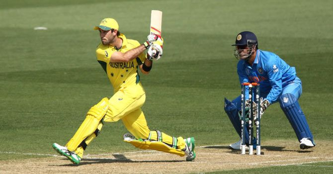 Australia's Glenn Maxwell plays a reverse-sweep as India 'keeper and captain Mahendra Singh Dhoni looks on