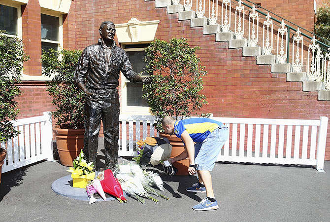 Tributes are placed at the statue of Richie Beanud at the Sydney Cricket Ground on Friday
