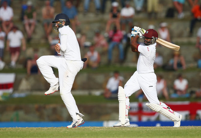 Darren Bravo of West Indies plays a shot as Joe Root of England takes evasive action