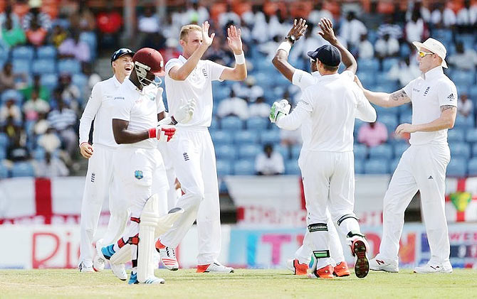 England's Stuart Broad celebrates with teammates after taking the wicket of West Indies' Kemar Roach
