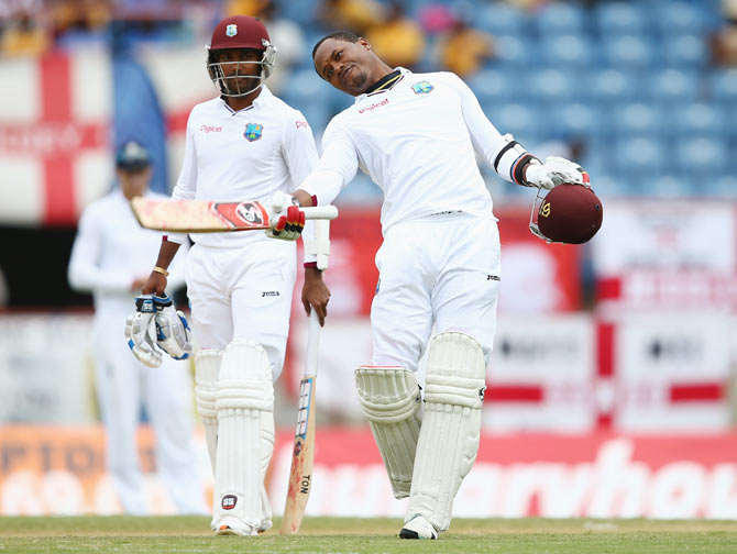 West Indies' Marlon Samuels (right) celebrates reaching his century with captain Denesh Ramdin (left)