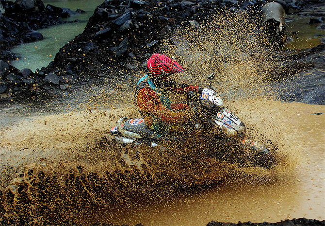 A rider is drenched in slush as he tries to negotiate a puddle