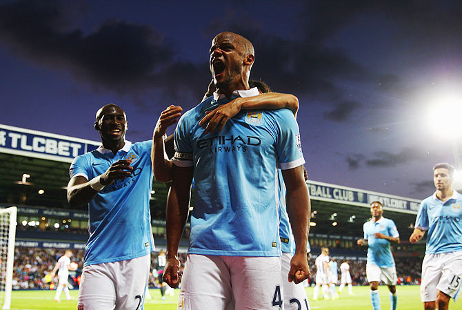Manchester City's Vincent Kompany (right) is ecstatic as he celebrates their third goal of the night against West Bromwich Albion on Monday, August 10
