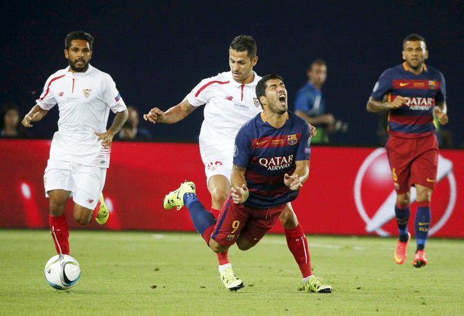 Barcelona's Luis Suarez (centre front) is fouled by Sevilla's Vitolo during their UEFA Super Cup match at Boris Paichadze Dinamo Arena in Tbilisi, Georgia, on Tuesday, August 11, 2015