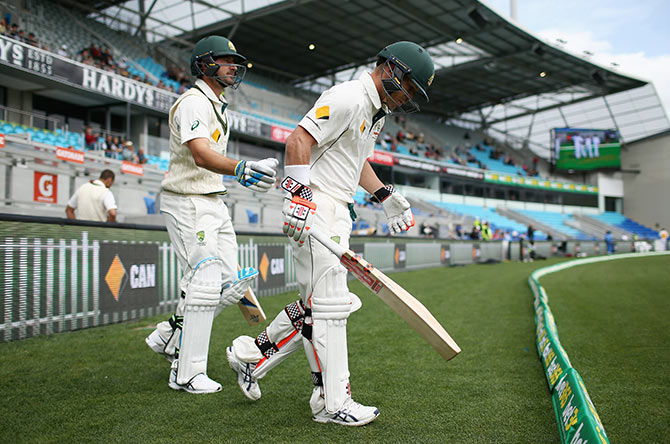 David Warner and Joe Burns of Australia run onto the field