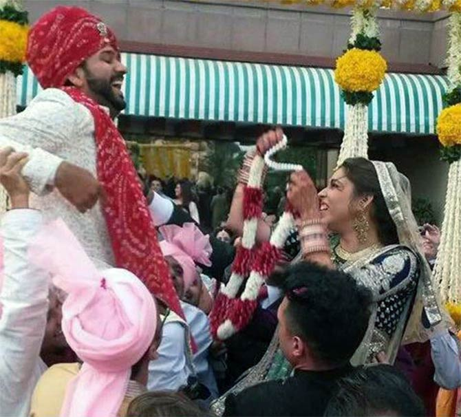 Rohit Sharma's friends lift him as bride Ritika tries to put the garland around his neck