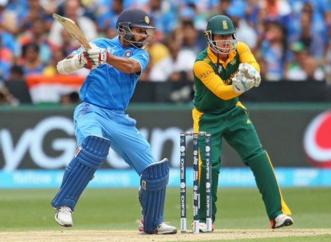Shikhar Dhawan of India hits a boundary as wicketkeeper Quinton de Kock of South Africa looks on