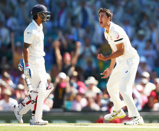 Mitchell Starc of Australia celebrates taking the wicket of Murali Vijay