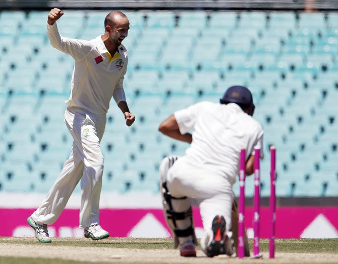 Australia's Nathan Lyon (left) celebrates after having Rohit Sharma bowled out for 53