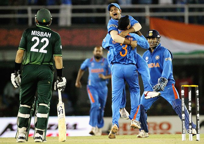 Suresh Raina of India leaps into the arms of team mate Harbhajan Singh with MS Dhoni (right) ad Misbah-ul-Haq of Pakistan looking on during the 2011 World Cup semi-final in Mohali.