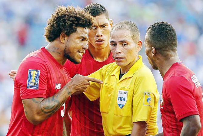 Panama defender Roman Torres (left) argues with referee Marlon Mejia after a penalty was awarded to Honduras