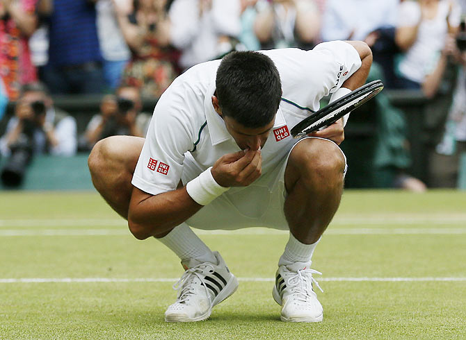 Serbia's Novak Djokovic eats some grass off Centre Court after winning his men's singles final against Switzerland's Roger Federer at the Wimbledon Tennis Championships in London on Sunday