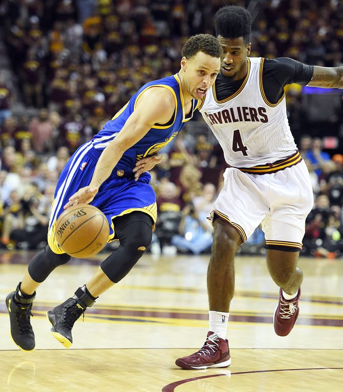 Golden State Warriors guard Stephen Curry (left) drives to the basket against Cleveland Cavaliers guard Iman Shumpert