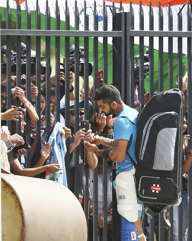 India's batting star Virat Kohli signs autographs for fans during the team's nets session at Sydney Cricket Ground on Wednesday