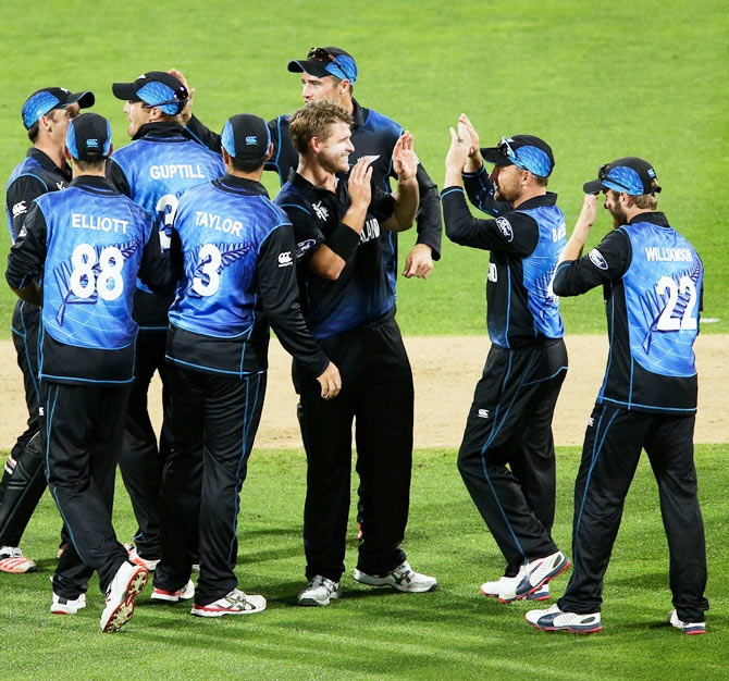New Zealand's Corey Anderson is congratulated by captain Brendon McCullum and teammates after taking a wicket