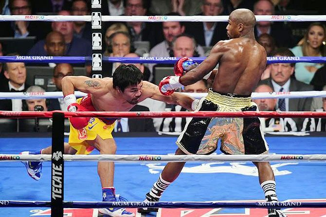 Manny Pacquiao lands a punch against Floyd Mayweather, Jr. (right)