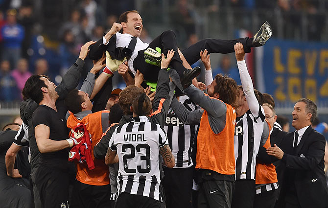 Massimiliano Allegri head coach of Juventus FC is lifted by his players after their title win on Saturday