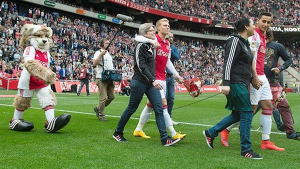 Ajax players walk on to the pitch with their mothers to celebrate Mother's Day on Sunday
