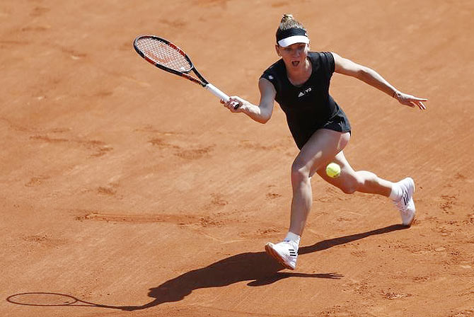 Romanian Simona Halep plays a shot against Russia's Evgeniya Rodina during their first round women's singles match at the French Open tennis tournament at the Roland Garros stadium in Paris on Sunday