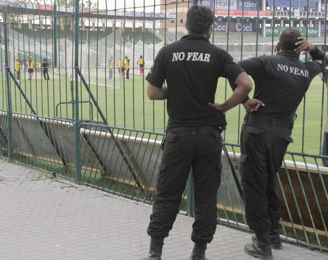 Police watch as members of the Zimbabwe cricket team practise